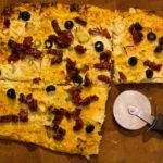 Karfiol Flammkuchen mit Oliven, Frühlingszwiebel und getrockneten Tomaten