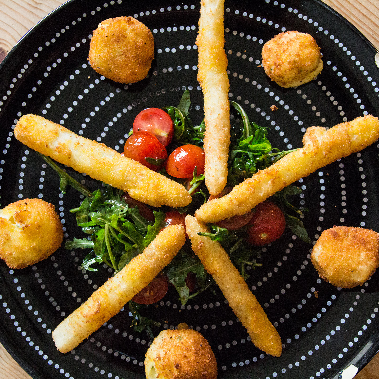 Panierte Spargelspitzen und Mozzarellabällchen auf Tomaten-Rucolasalat